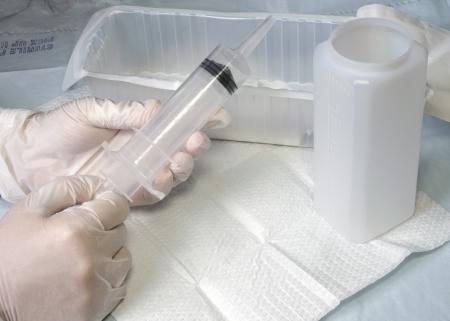 Nurse preparing irrigation syringe.