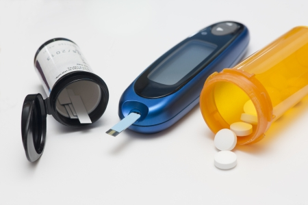 Glucometer, test strips, and diabetes medication. photo