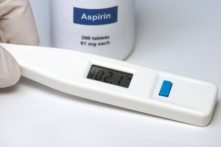 Nurse holds thermometer with high temperature with aspirin in background. Stock fotó
