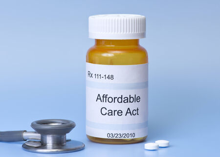 Affordable Care Act prescription bottle on blue with sethescope and pills  photo