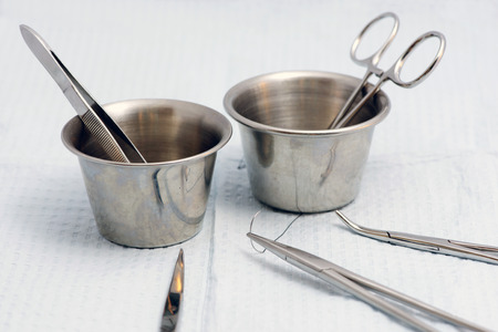 surgical needle: Surgical instruments with medicine cups and suture.