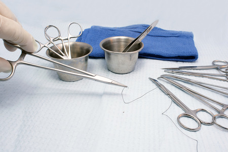 Surgeon selects a needle holder with suture. photo