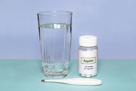 aspirin: Aspirin bottle with thermometer and glass of water.