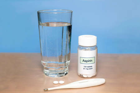 aspirin: Aspirin bottle with thermometer and glass of water on tabletop.