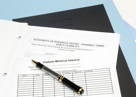 Verklaring van persoonlijk letsel formulier met patiënt grafiek en pen. Stockfoto