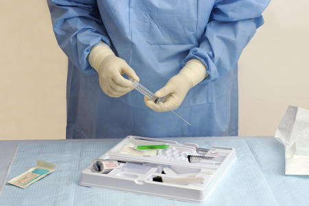catheter: Nurse prepares syringe with trocar catheter surgical kit.
