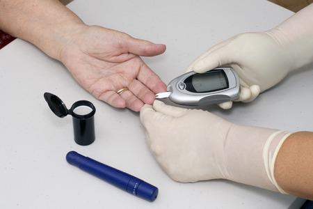Home health nurse tests patients blood sugar. photo