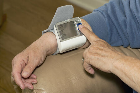 blood pressure cuff: Senior patient places blood pressure monitor on wrist to measure hypertension.