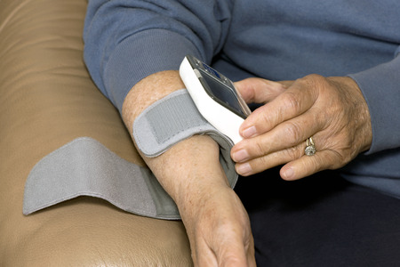 cuff: Senior patient places blood pressure monitor on wrist to measure hypertension.