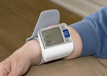 Senior patient with blood pressure monitor on wrist to measure hypertension. Stock Photo