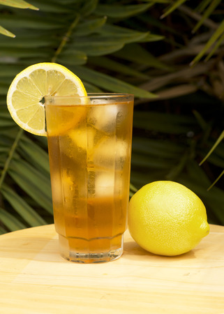 Iced tea in a glass with lemon outdoors.