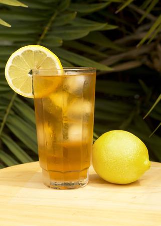 iced tea: Iced tea in a glass with lemon outdoors.