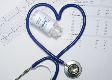 Aspirin bottle with heart shaped stethoscope, electrocardiograph, and lab report.