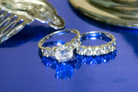 platinum wedding ring: Wedding and engagement rings with silver comb on blue. Stock Photo