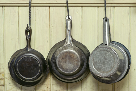 cooking pot: Old iron skillets and antique pans hang on iron hooks against a wall. Stock Photo