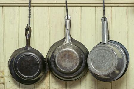 steel pan: Sartenes de hierro antiguas y sartenes antiguos cuelgan de ganchos de hierro contra una pared.