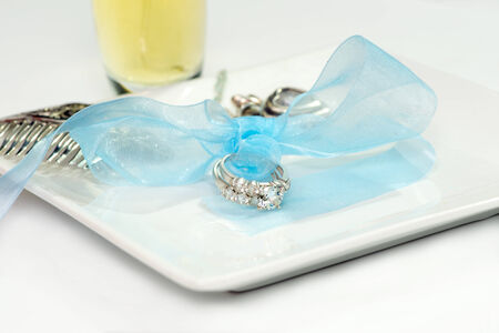 Wedding rings tied with a blue bow with perfume bottle and silver hair comb. photo