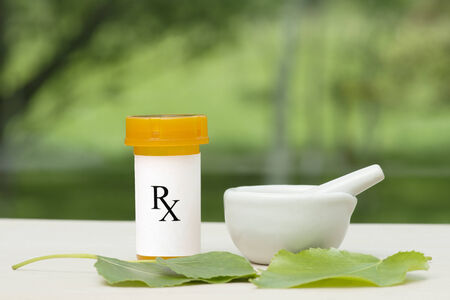 Prescription bottle with mortar, pestle, and green leaves.