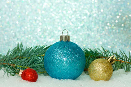 boughs: Red, blue and gold Christmas ornaments with spruce boughs on a sparkle background.