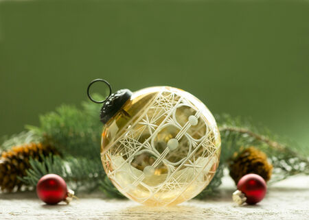 kugel: Antique amber cut glass Christmas ornament with spruce and cones.