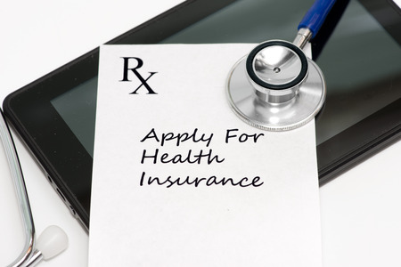 Prescription to apply for health insurance with personal computing tablet and stethoscope.