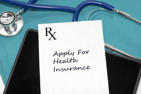 Prescription to apply for health insurance with personal computing device and stethoscope on scrubs.