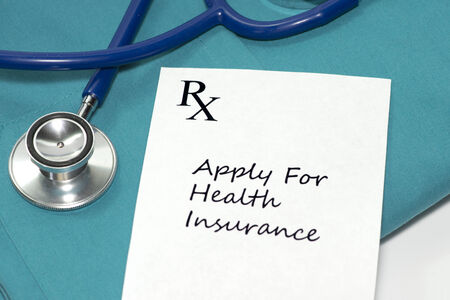 Prescription to apply for health insurance with stethoscope on scrubs.