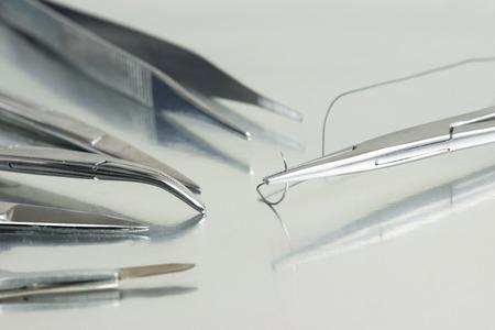 coser: El soporte de aguja de sutura con instrumentos quirúrgicos y en la bandeja estéril. Foto de archivo