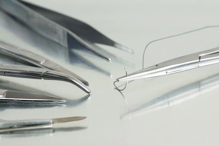 suture: Needle holder with suture and surgical instruments on sterile tray.