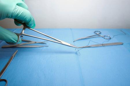 pinzas: Soporte de la aguja con la sutura recogido de campo estéril por el técnico. Foto de archivo