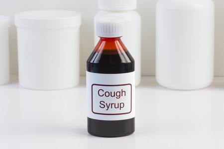 Cough medicine in amber bottle with white conatiners in background.