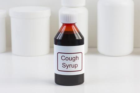 toser: Medicina para la tos en botella ámbar con conatiners blancas en el fondo. Foto de archivo