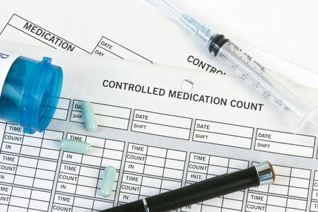 Controlled medication form with pen and prescription pills. Stockfoto