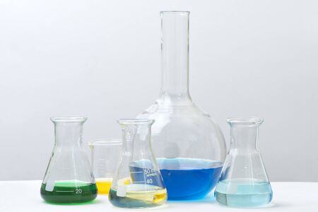 reagents: Different colored lchemical reagents in laboratory glassware. Stock Photo