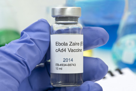 Ebola Zaire vaccine held by technician with laboratory research equipment. photo