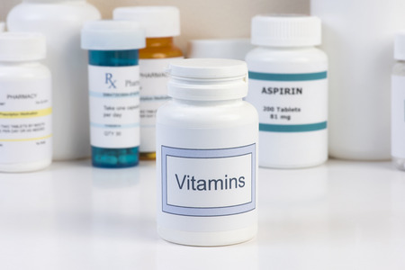 Vitamin bottle on countertop with prescription bottles in background. Stok Fotoğraf