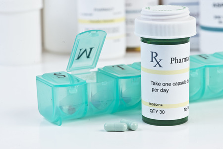 Daily medication dispenser with green prescription bottle and pills. Zdjęcie Seryjne