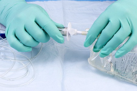 Nurse prepares IV solution for infusion. Stock Photo