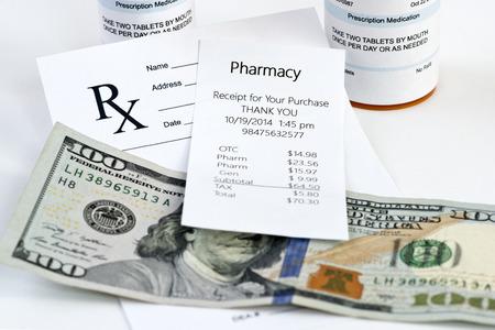 Recibo de la farmacia con la botella de la prescripción y la prescripción en el fondo neutro.