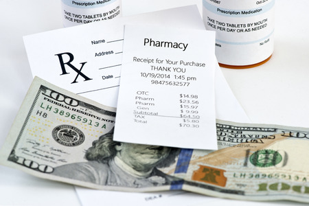 Pharmacy receipt with prescription bottle and prescription on neutral background.