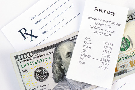 medical bill: Receipt for pharmacy purchase with prescription and one hundred dollar bill.