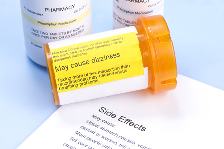 Prescription bottle with warning label and drug side effects print out.