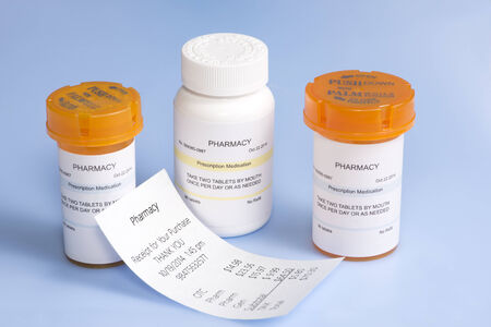 high cost of healthcare: Pharmacy reciept with prescription bottles on blue.