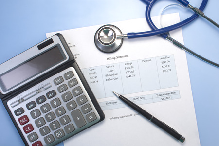 Health care billing statement with stethoscope, pen and calculator.