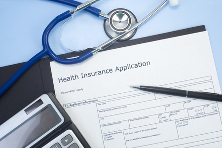 doctor money: Application for health insurance with stethoscope, calculator, and pen. Stock Photo