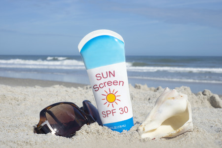 Bottle of sunscreen with shell and sunglasses on beach.