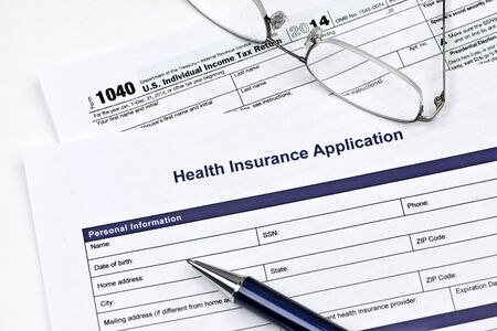health care costs: Health insurance application with United States 1040 tax form.