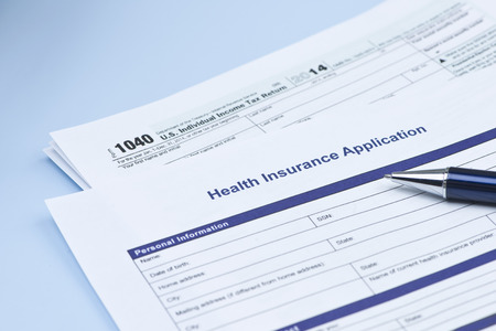 health insurance: Health insurance application with United States 1040 tax form and pen.