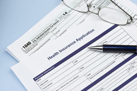 salud: Solicitud de seguro de salud con Estados Unidos 1040 formulario de impuestos con gafas y la pluma. Foto de archivo