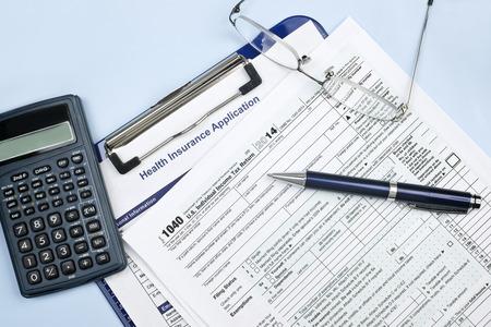 健康保険アプリケーション 1040年米国の税務フォーム、メガネ、電卓。